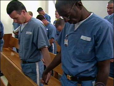 Inmates join hands during a religious ceremony behind bars
