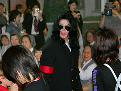 Michael Jackson, center, leaves an orphanage gymnasium after meeting more than 160 children and nuns in Tokyo on Sunday, May 28, 2006.