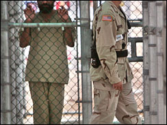 A detainee, name, nationality, and facial identification not permitted, holds onto a fence as a U.S. military guard walks past, within the grounds of the maximum security prison at Camp 5