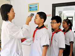 A medical worker checks the temperature of students to identify symptoms of the H1N1 flu on the first day of their new semester at a middle school in Shanghai, China, Tuesday, 1 September 2009.