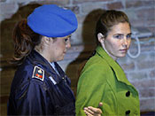 U.S. murder suspect Amanda Knox in accompanied by a penitentiary police officer at the court in Perugia, Italy, Friday, Dec. 4, 2009.