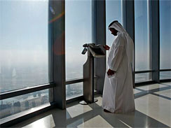 An Emirati man watches the city view at an observation point screen at the observation deck of the Burj Dubai tower, on Level 124 in Dubai, United Arab Emirates, Monday, Jan. 4, 2010.