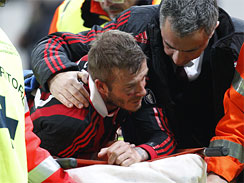 AC Milan English soccer star David Beckham leaves the pitch after being injured during the Serie A soccer match between AC Milan and Chievo at the San Siro stadium in Milan, Italy, March 14, 2010.