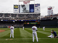 Minnesota Twins players wear the number 42 on their jerseys in honor of Jackie Robinson as a tribute to Robinson plays on the scoreboard prior to the Twins baseball game against the Boston Red Sox in Minneapolis, Thursday, April 15, 2010.
