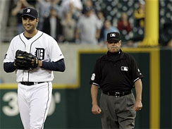 Detroit Tigers pitcher Armando Galarraga, left, smiles as he walks away from first base umpire Jim Joyce, right, who called Cleveland Indians' Jason Donald safe at first base in the ninth inning of a baseball game in Detroit, Wednesday, June 2, 2010. Galarraga lost his bid for a perfect game with two outs in the ninth inning on the disputed call at first base. Detroit won 3-0. (AP Photo/Paul Sancya)